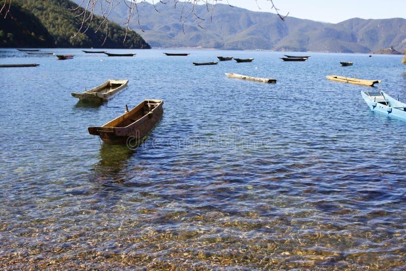 Massor av wood fiskebåt på Lugu för blått vatten som den sceniska fläcken för sjö omges av snöberget och hög himmel royaltyfri bild