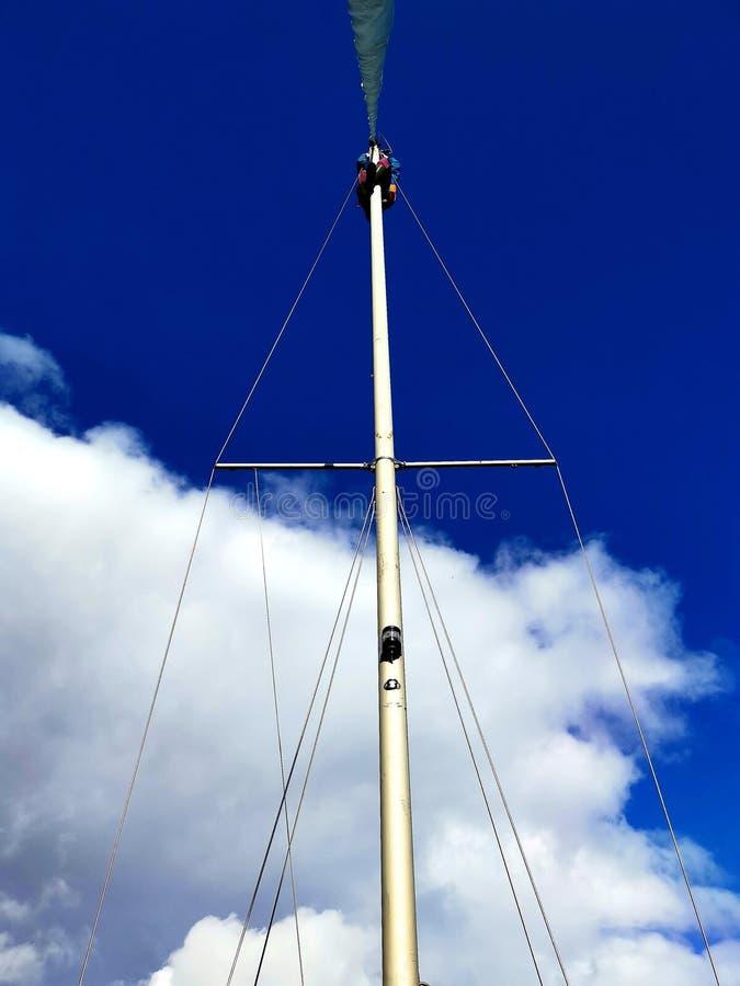 Mast de veleiro contra céu azul nublado imagem de stock royalty free