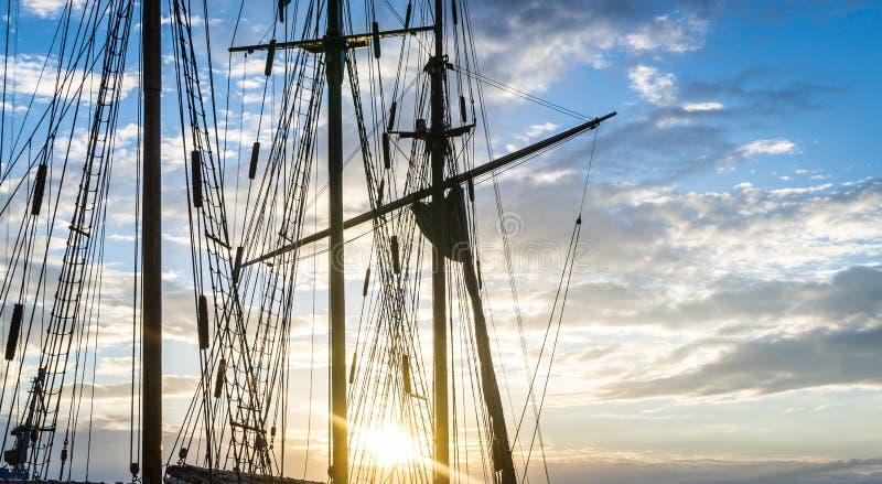 Mast en kabelzeilbootschip op de achtergrond van de hemelzonsondergang stock afbeelding