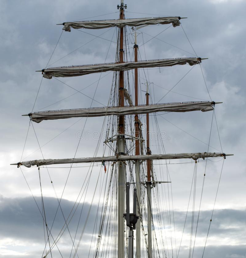 Mast, rigging and furled sails on a tall ship / sailing ship. Cloudy sky background stock images