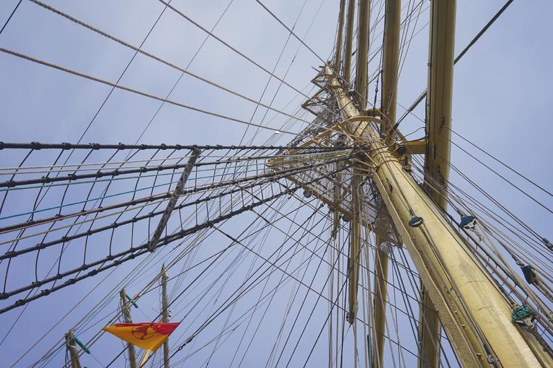 Mast with three look-outs. Mast with rigging of a large sailing ship from a frog`s perspective against a blue sky royalty free stock photography