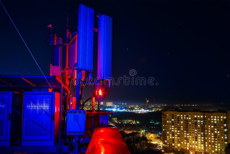 Mastantenn för mobila kommunikationer uppe på en högväxt byggnad, mot nattstad royaltyfri fotografi