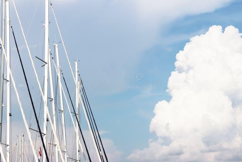 Maste von Segeljachten gegen den blauen Himmel belichtet durch den hellen Sonnenschein Technologien von Segeln- und KreuzfahrtCha stockfotografie