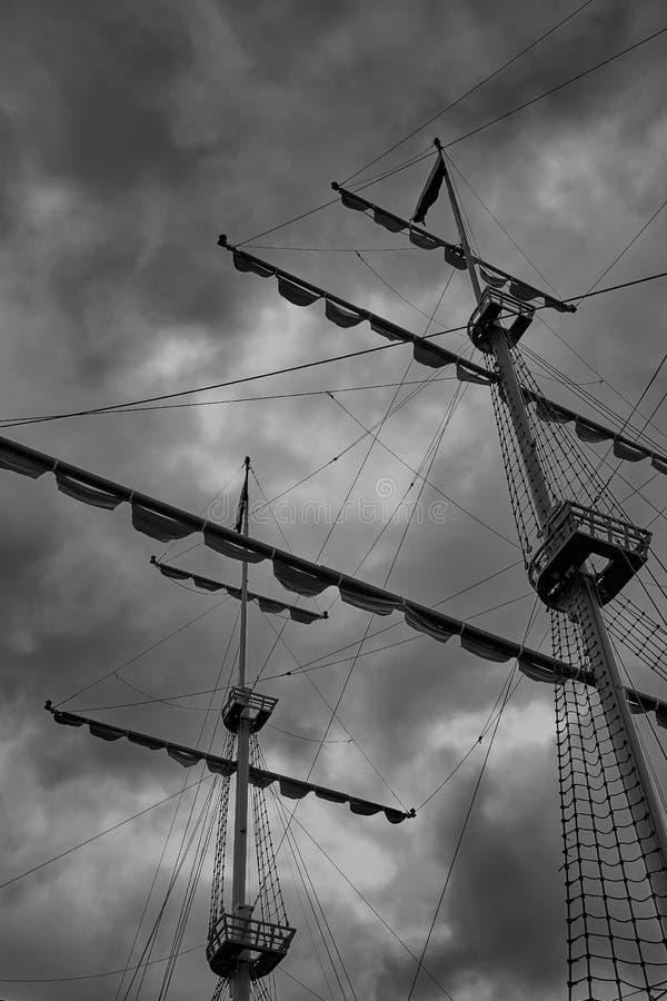 Masten av en gammal segelbåt mot bakgrunden av moln av en stormig himmel arkivfoto