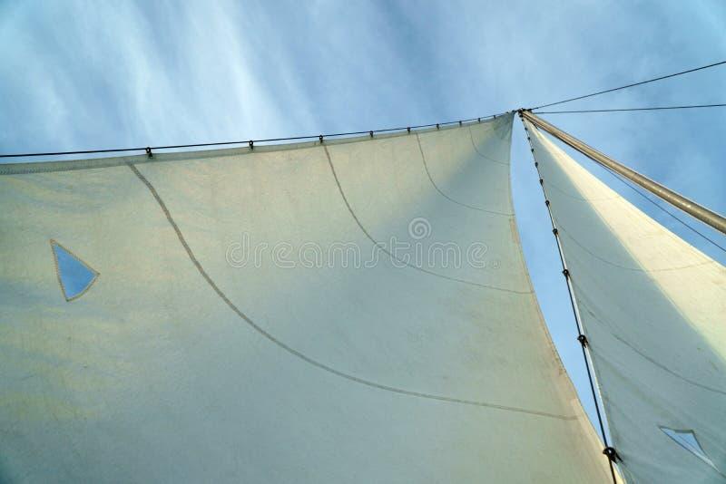 Masten och vit seglar av yachten mot blå molnig himmel, sikt från över royaltyfri foto
