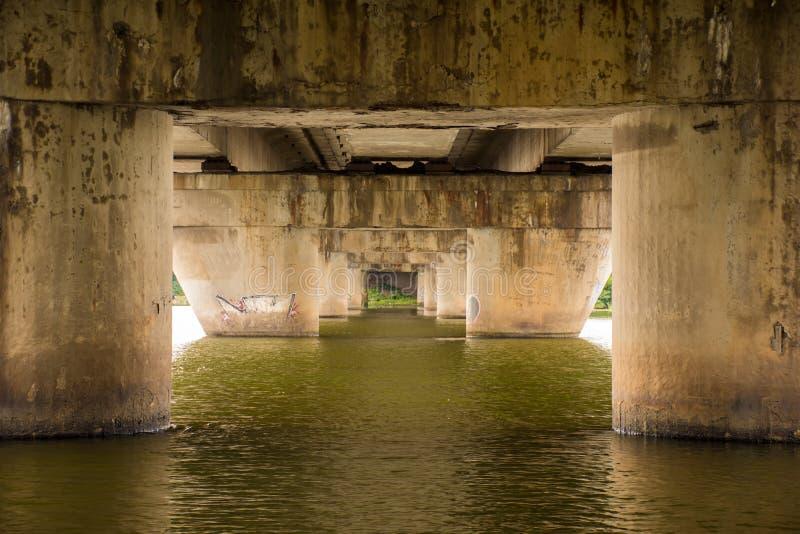 Masten oder konkrete Säule der Brücke im Wasser des Flusses, in einer geschwankten abwärts rückläufigen Art als a gegenüberstelle lizenzfreies stockbild
