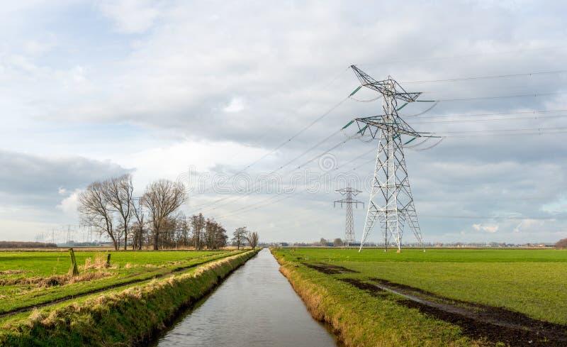 Masten und Kabel von einem Hochspannungsgitter in einem ländlichen Gebiet stockbild