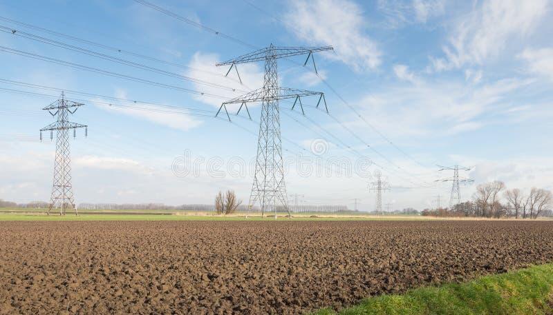 Masten und Stromleitungen von einem niederländischen Hochspannungsgitter lizenzfreies stockbild