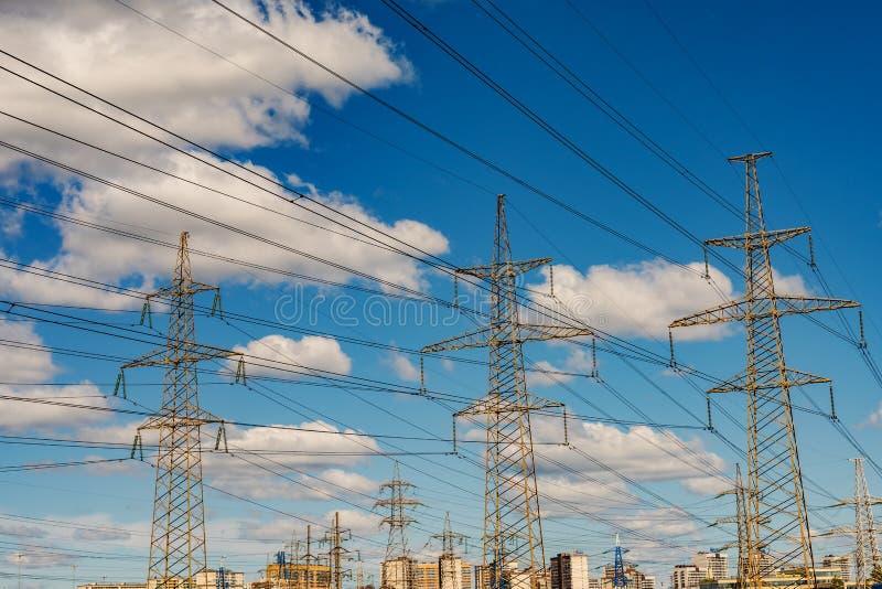 Masten van draden met hoog voltage op de achtergrond van de stad royalty-vrije stock foto's