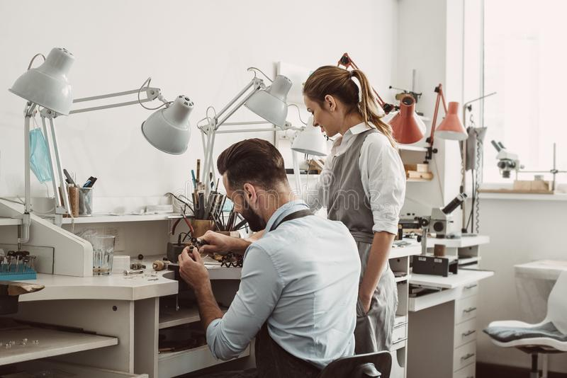 Master and apprentice. Young male assistant and female jeweler are working together at jewelry making workshop. stock photos