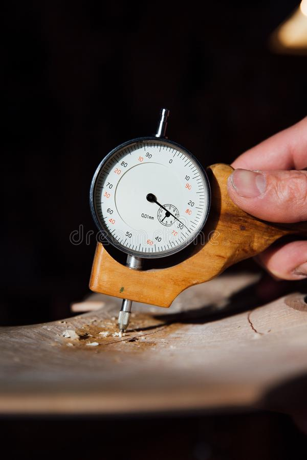 Master artisan luthier working on the creation of a violin. painstaking detailed work on wood. Master artisan luthier working on creation of violin. detailed royalty free stock photo