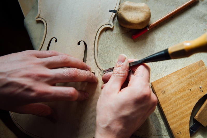 Master artisan luthier working on the creation of a violin. painstaking detailed work on wood. royalty free stock photos