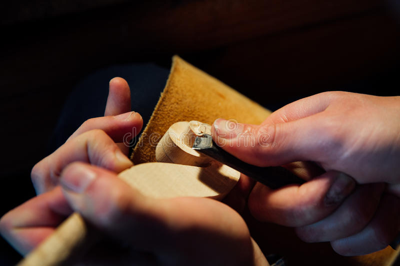 Master artisan luthier working on the creation of a violin. painstaking detailed work on wood. stock images
