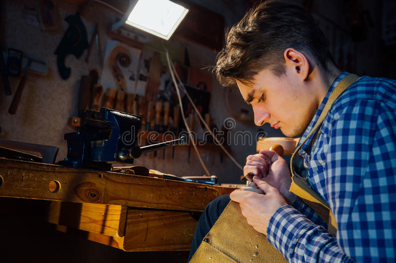 Master artisan luthier working on the creation of a violin. painstaking detailed work on wood. Master artisan luthier working on the creation of a violin scroll royalty free stock photo