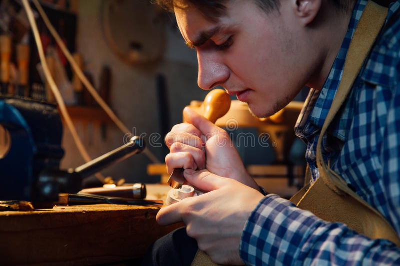 Master artisan luthier working on the creation of a violin. painstaking detailed work on wood. Master artisan luthier working on the creation of a violin scroll stock photos