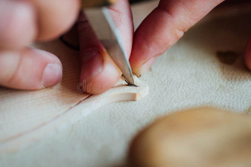 Master artisan luthier working on the creation of a violin. painstaking detailed work on wood. Master artisan luthier working on the creation of a violin royalty free stock photo