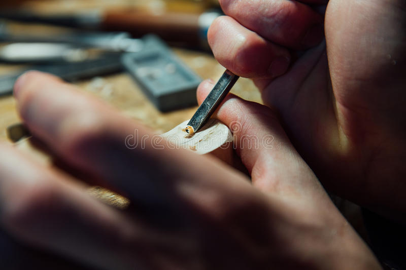 Master artisan luthier working on the creation of a violin. painstaking detailed work on wood. royalty free stock photography