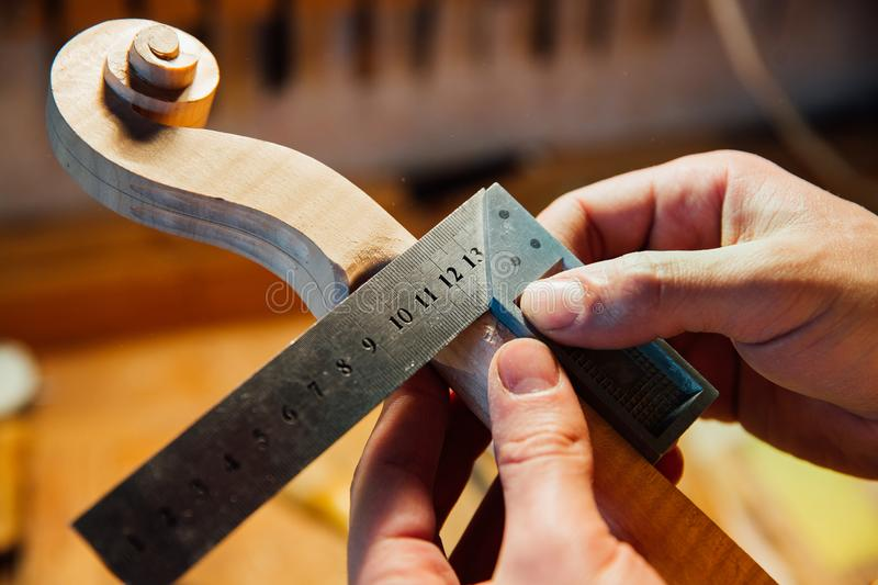 Master artisan luthier working on creation of a violin scroll. detailed work on wood with tools. Men`s hands Measures the thickness of the scroll with meter stock photos