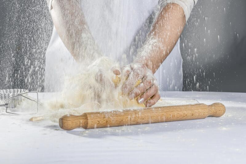Master baker kneads culinary dough for the manufacture of confectionery royalty free stock photos