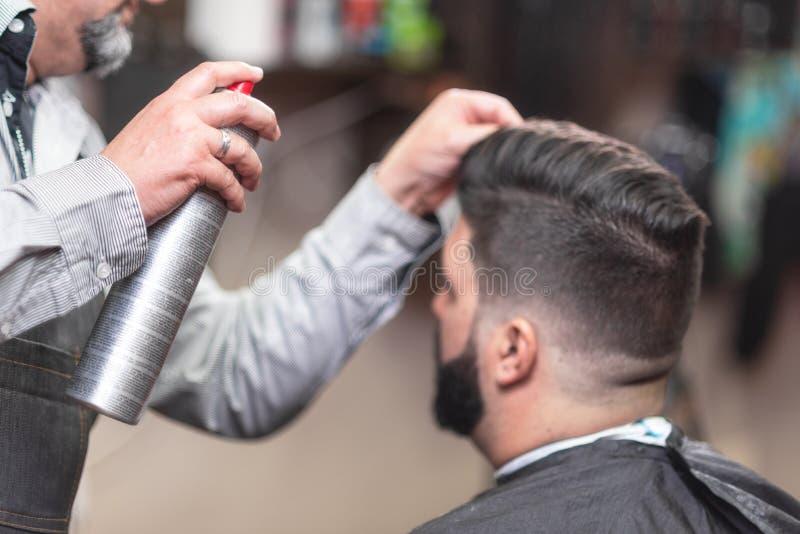 Master barber making modern hairstyle fixating hair with spray. Master barber making modern hairstyle fixating hair with spray stock photography