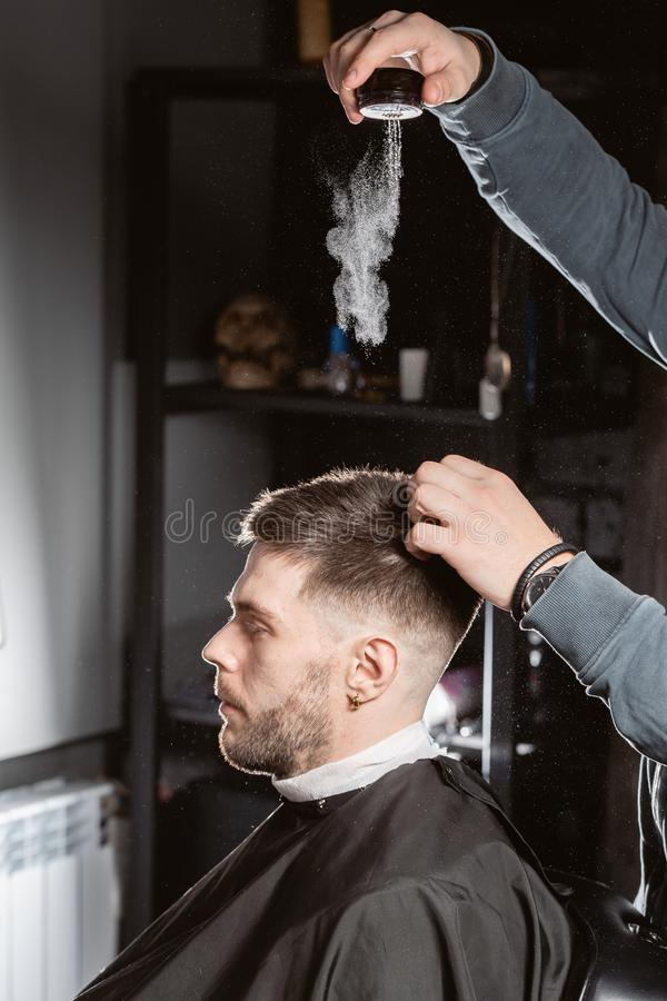 Master barber pours out styling powder to fix hair. hairdresser makes hairstyle for a young man. Hair cutting with metal scissors. Master cuts hair and beard of royalty free stock image