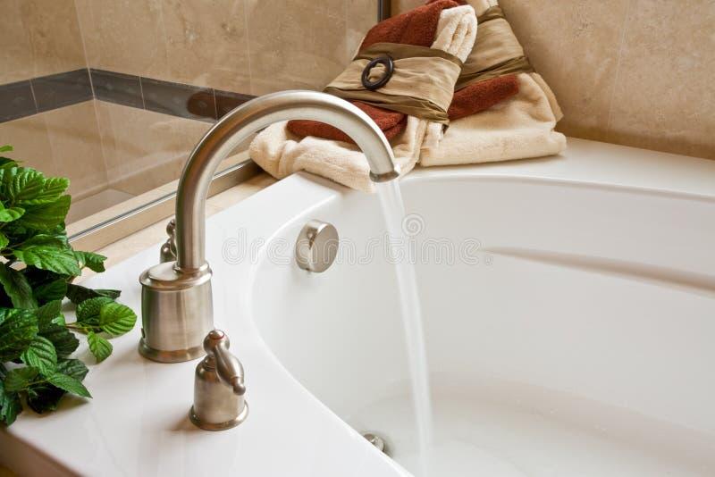 Master bathroom bathtub with running water stock photos