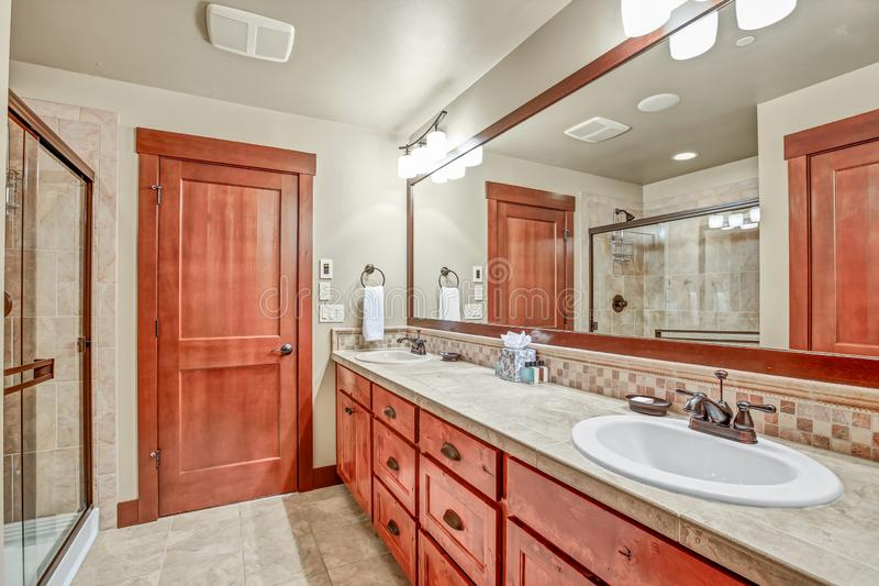 Master bathroom with double sink vanity cabinet. Master bathroom with double sink vanity cabinet and wood framed mirror. Northwest, USA royalty free stock photos
