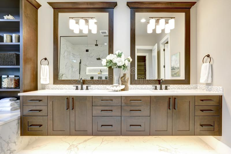 Master bathroom interior in luxury modern home with dark hardwood cabinets, white tub and glass door shower royalty free stock photo