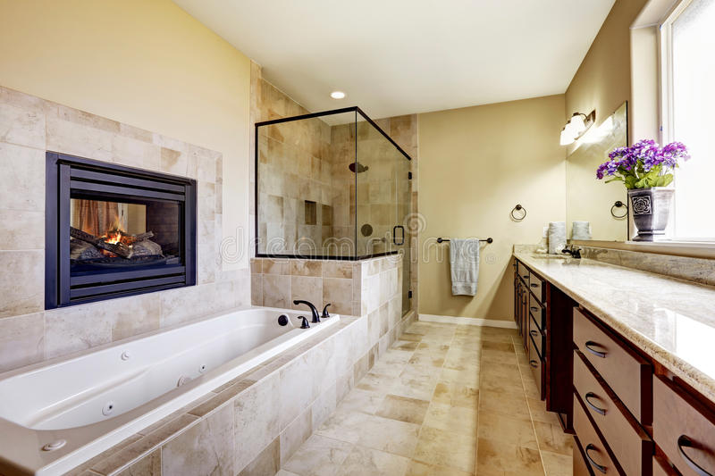 Master bathroom in modern house with fireplace and tile floor. Master bathroom in modern house with fireplace, bath tub with tile trim, glass shower and modern stock photos