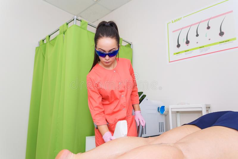 Master beautician removes hair with laser hair removal. The procedure of laser hair removal of the legs royalty free stock photography