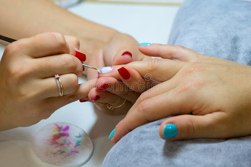 Master in a beauty salon doing manicures girl stock image