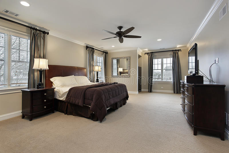 Master bedroom with dark wood furniture. Master bedroom in luxury home with dark wood furniture stock photography