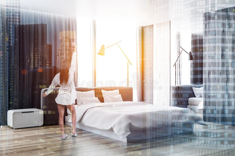 Master bedroom interior, woman in pajamas. Woman in pajamas stretching in the morning in master bedroom with a panoramic window. Luxury lifestyle and interior royalty free stock photography