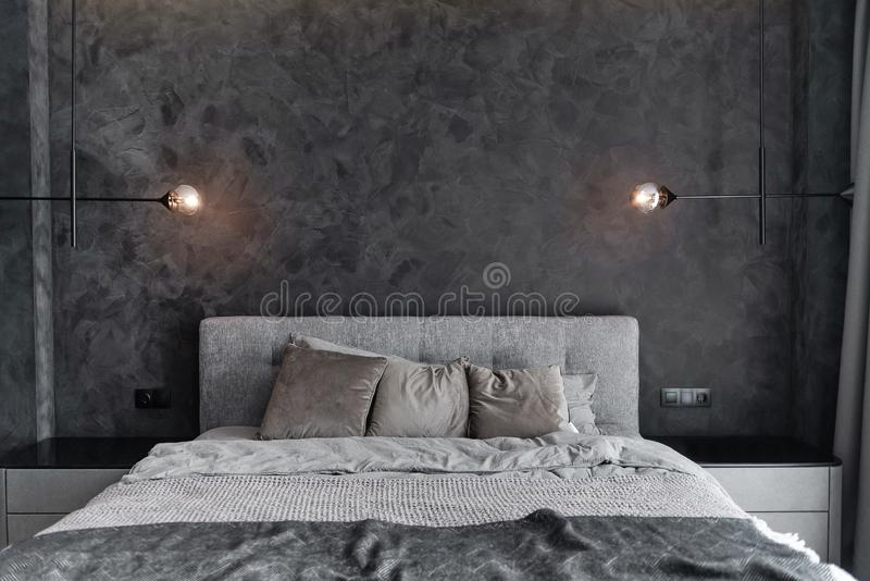 Master bedroom for a lonely stylish man, a bachelor. Modern room with trendy gray interiors, large king-size and lamps. Master bedroom for a lonely stylish man royalty free stock photos