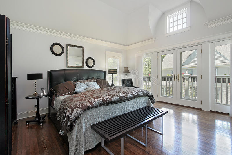 Master bedroom in luxury home with balcony stock photography