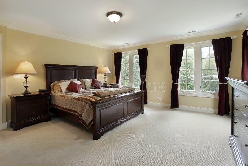 Master bedroom with mahogany furniture. Master bedroom in luxury home with mahogany furniture royalty free stock photography