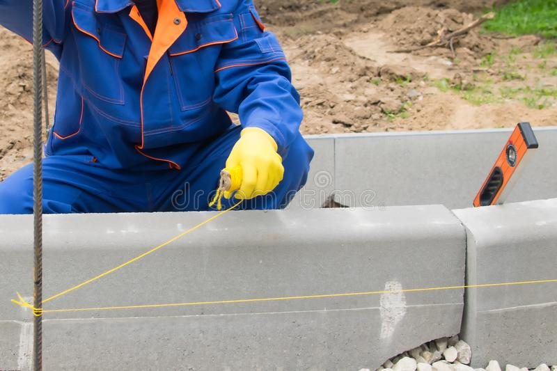 Master in blue form sets the control thread, for smooth laying of curbstone, close-up royalty free stock photography