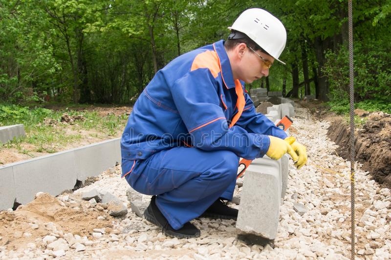 Master in blue form sets the control thread for smooth laying of curbstone stock photography