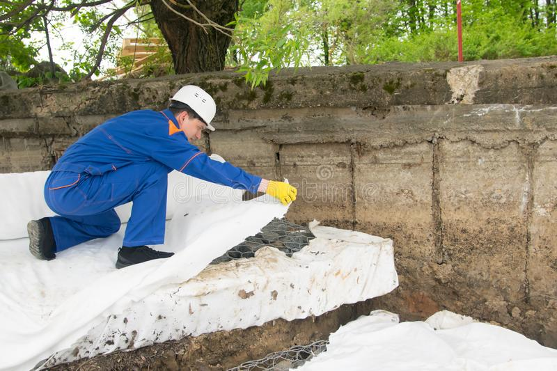 Master in blue uniform and protective helmet, puts protective cloth to insulate different materials, stones and soil from each. Other stock photo