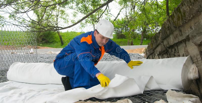 Master in blue uniform, puts protective cloth to insulate different materials, stones and soil from each other stock images