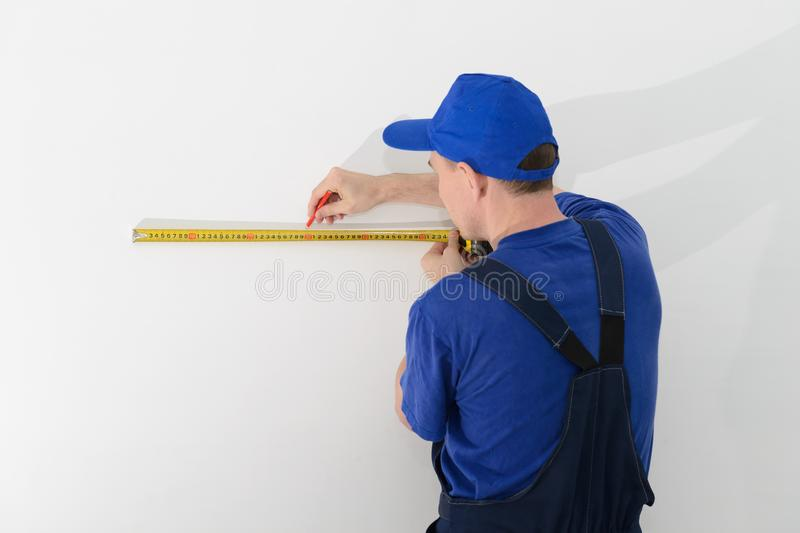 Master builder in uniform of measuring distances on wall with a tape measure stock image