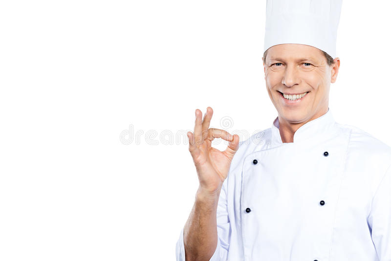 Master chef. Confident mature chef in white uniform gesturing OK sign and smiling while standing against white background stock images