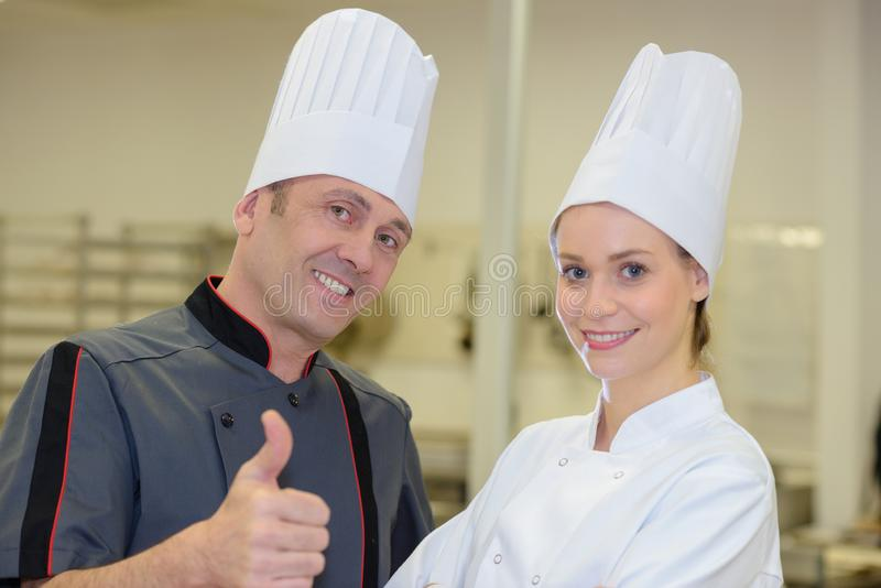Master chefs giving thumbs up with colleague. A master chefs giving thumbs up with colleague royalty free stock image