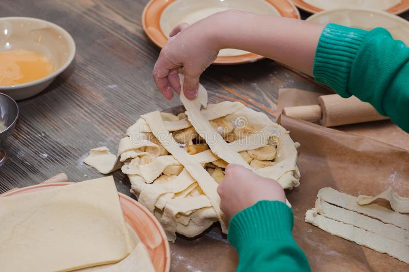 Master class for children on baking pie. Young children learn to cook a sweet pie. Kids preparing homemade pie. Little cook stock images