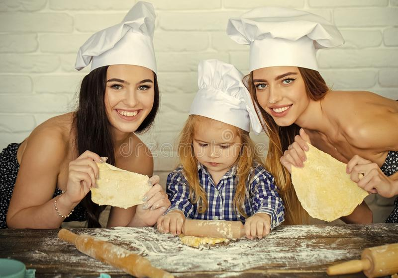 Master class for cooking. Child and women rolling dough on table stock images