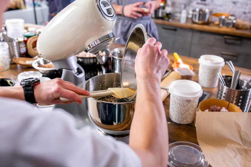 Master class in the kitchen. The process of cooking. Cook puts ingredients into a blender. Step by step. Tutorial. Close-up royalty free stock images