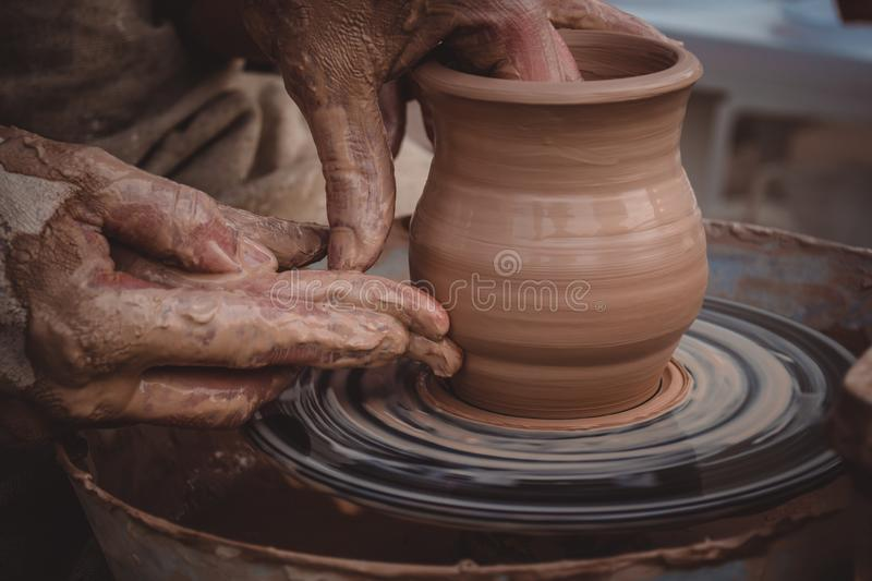 Master class on modeling of clay on a potter`s wheel. In the pottery workshop stock photography