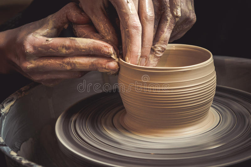 Master class on modeling of clay on a potter`s wheel. In the pottery workshop stock photo