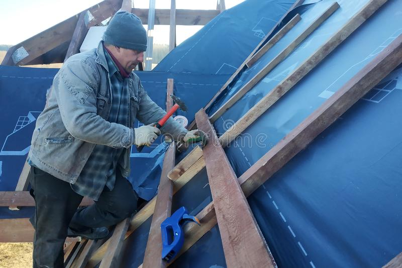 The master clogs the nail into a beam, fixing this gidrorizer to the rafters royalty free stock photo