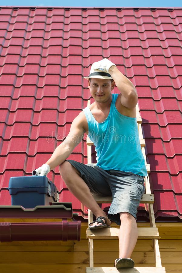 Master comes down from the roof of the house with tools after repairing it stock photos